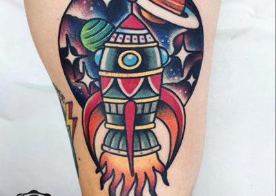 tatuajes old school de un cohete con planetas