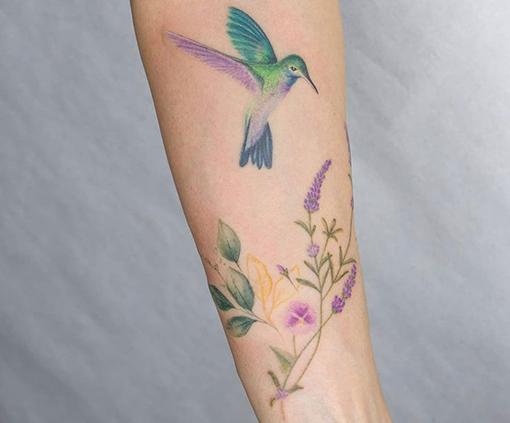 tatuaje en el brazo mujer de colibri