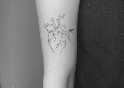 tatuajes finos de un corazón con flores